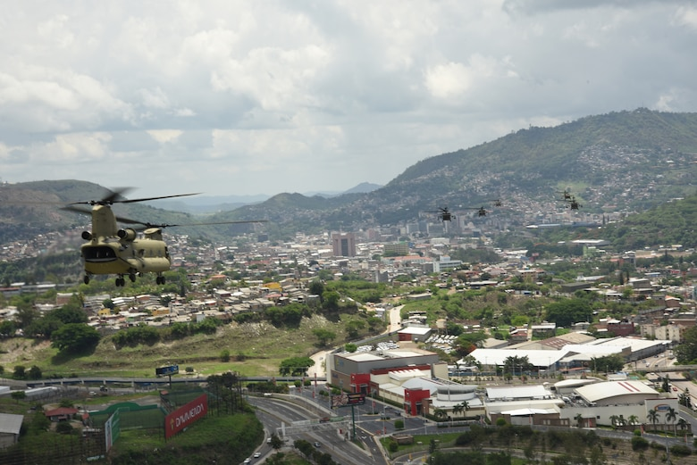U.S. Army aircraft assigned to the 1st Battalion, 228th Aviation Regiment fly over a metropolitan area in the skies of Central America during a 10-aircraft formation exercise.