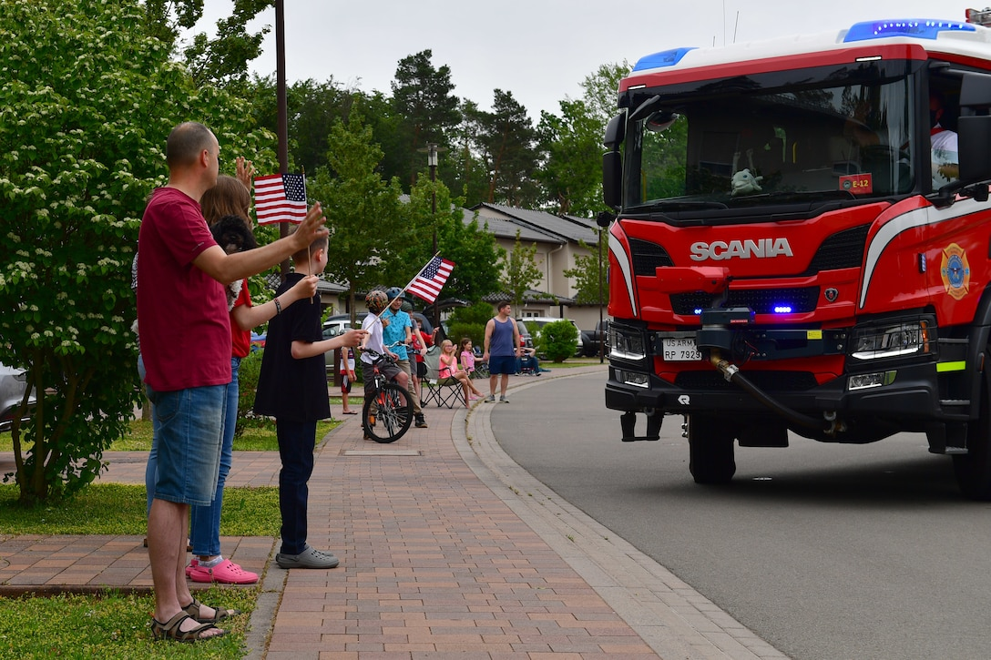 Military families stand on a sidewalk and wave to a passing fire truck.