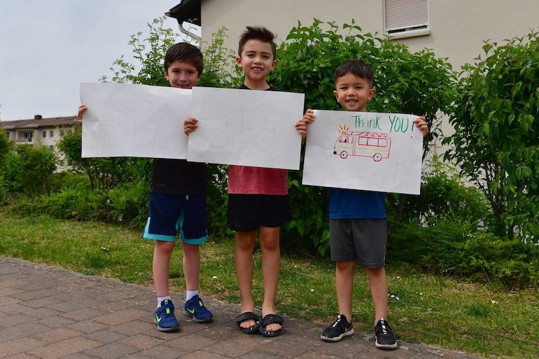 Three children hold thank you signs for first responders.