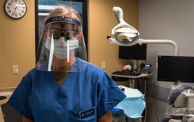 Lt. Col. Rachel A. Webber, 2nd Operational Medical Readiness Squadron periodontist, stands in a dental suite with her personal protective equipment at Barksdale Air Force Base, La., May 26, 2020.  All dentists and dental technicians working on or around patients will be wearing fitted face masks, hair coverings and gowns as part of the dental clinics safety procedures. (U.S. Air Force photo by 2nd Lt. Aileen Lauer)