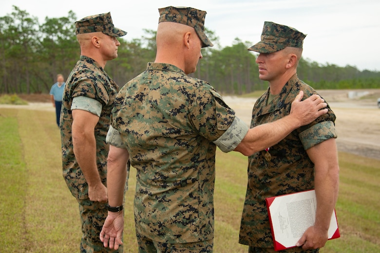 U.S. Marine Corps Maj. Gen. Julian D. Alford, center, commanding general, Marine Corps Installations East-Marine Corps Base Camp Lejeune, awards Gunnery Sgt. Jonathan E. Hill, right, heavy equipment chief with 2nd Combat Engineer Battalion, MCB Camp Lejeune, the Meritorious Achievement Medal on MCB Camp Lejeune, North Carolina, Oct. 29, 2020. Hill received the award for his efforts in building the G-36 Company Battle Course Range. G-36 has been redesigned to enable company commanders to train with organic weapons systems and attachments they would have available during combat and conduct full-scale operations on one range. (U.S. Marine Corps photo by Cpl. Ginnie Lee)