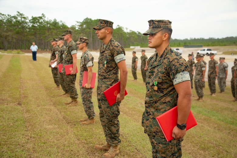 U.S. Marines with 2nd Combat Engineer Battalion and 8th Engineer Support Battalion stand at attention during an awards ceremony at the site of the G-36 Company Battle Course Range on Marine Corps Base Camp Lejeune, North Carolina, Oct. 29, 2020. Maj. Gen. Julian D. Alford, commanding general Marine Corps Installations East-Marine Corps Base Camp Lejeune, awarded the Marines the Navy and Marine Corps Commendation Medal for their efforts in building the range. G-36 has been redesigned to enable company commanders to train with organic weapons systems and attachments they would have available while forward deployed and  conduct full-scale operations on one range.  (U.S. Marine Corps photo by Cpl. Ginnie Lee)