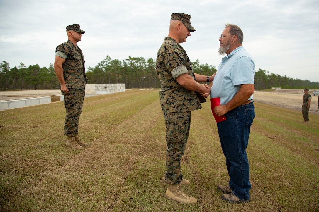 U.S. Marine Corps Maj. Gen. Julian D. Alford, left, commanding general, Marine Corps Installations East-Marine Corps Base Camp Lejeune, presents a letter of appreciation to Fredrick L. Small, the range developmental progress officer for MCB Camp Lejeune, during an awards ceremony on MCB Camp Lejeune, North Carolina, Oct. 29, 2020. Small received the letter for his efforts during the planning and transformation of the G-36 Company Battle Course Range. G-36 has been redesigned to enable company commanders to train with organic weapons systems and attachments they would have available during combat and conduct full-scale operations on one range. (U.S. Marine Corps photo by Cpl. Ginnie Lee)