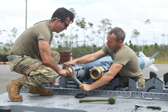 Two Airmen work to disassemble a bomb.