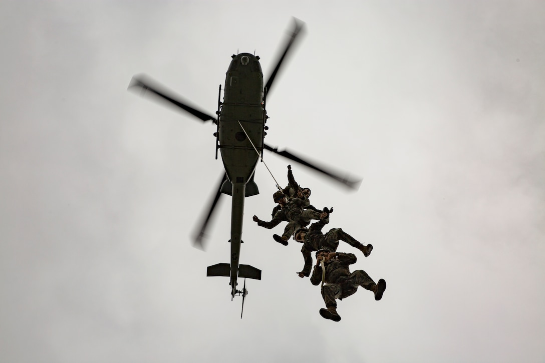 A group of Marines hold on to a rope outside of an airborne helicopter.