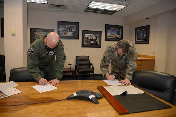 U.S. Air Force Col. David Berkland, the 354th Fighter Wing (FW) commander, and Chief Master Sgt. John Lokken, the 354th FW command chief, sign Combined Federal Campaign (CFC) donation slips on Eielson Air Force Base, Alaska, Oct. 28, 2020.