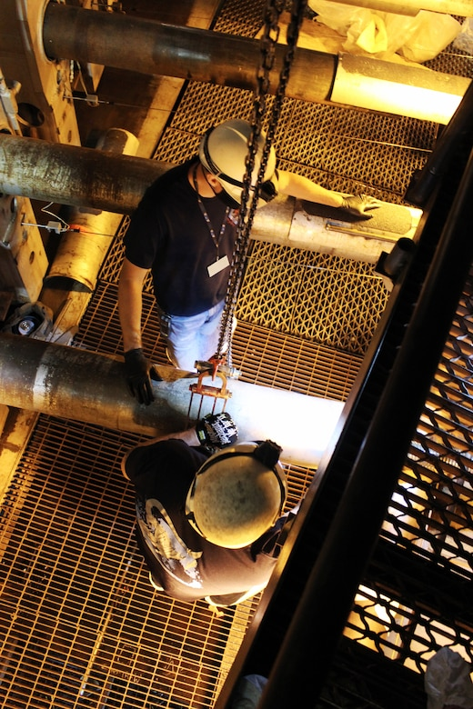 Outside machinists Todd Robison, top, and Troy Jernigan inspect a ball screw for one of the jacks on the plenum side of the nozzle of the Arnold Engineering Development Complex 16-foot supersonic wind tunnel Sept. 25, 2020, at Arnold Air Force Base, Tenn. These jacks are driven to precise locations by the nozzle motors to set correct contours for creating supersonic flow on the air side of the nozzle. (U.S. Air Force photo by Deidre Moon) (This photo has been altered by obscuring a badge for security purposes.)