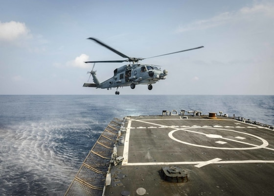 An MH-60R Sea Hawk helicopter from the Royal Australian Navy Anzac-class frigate HMAS Ballarat (FFH 155) prepares to land on the flight deck aboard the Arleigh Burke-class guided-missile destroyer USS John S. McCain (DDG 56) during flight operations. McCain is assigned to Destroyer Squadron Fifteen (DESRON 15), the Navy's largest forward-deployed DESRON and the U.S. 7th Fleet's principal surface force.