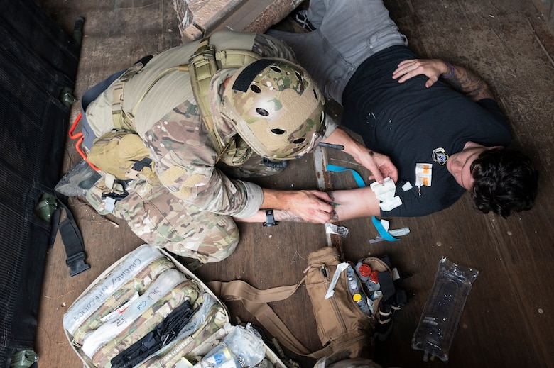 We look down from above at a Special Tactics Operator applying a dressing to a victim's left arm during training.