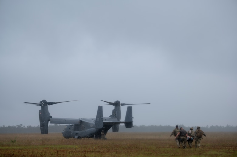 Four Special Tactics Operators carry a patient on a stretcher to a waiting dual-rotor helicopter waiting in a field.