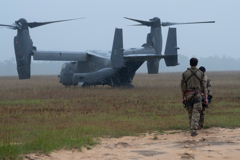 Two Special Tactics Operators carry a patient on a stretcher to a waiting dual-rotor helicopter waiting in a field.
