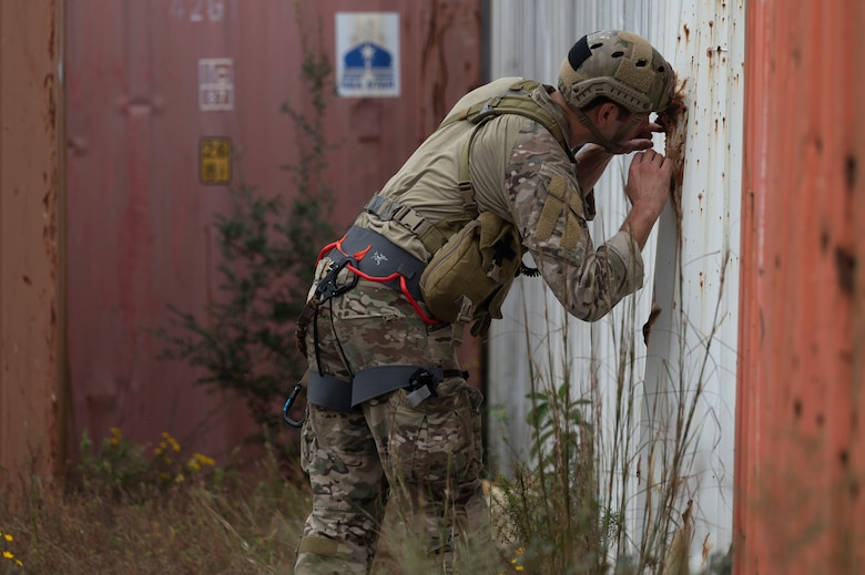We look at the side of a Special Tactics Operator as he leans over with his helmet against a corrugated metal wall as he looks for injured civilians through a hole in the wall.