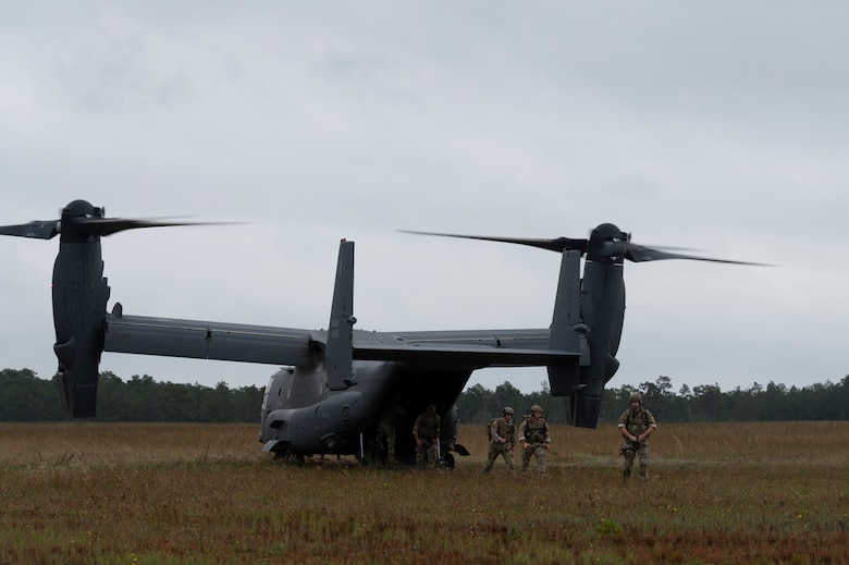 Three Special Tactics operators have just walked off of the ramp of a dual-rotor helicopter in the middle of a field.