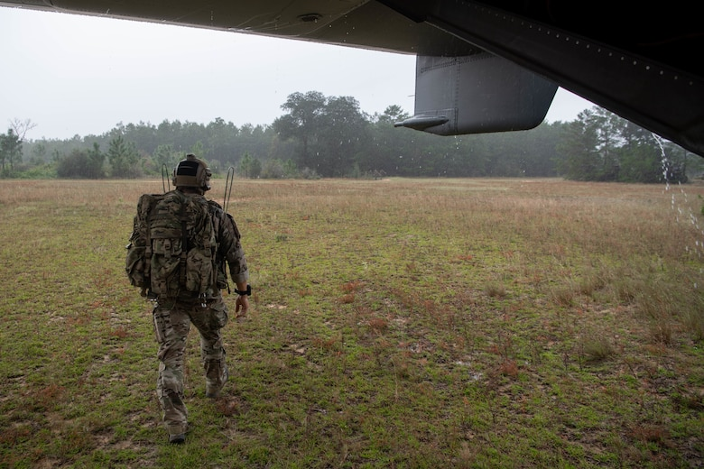 A single Special Tactics Operator with heavy pack walks away from us under the tail of a helicopter towards a simulated disaster site in the tree line in the distance.
