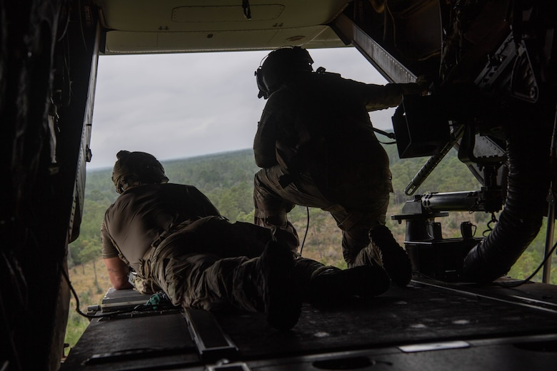 As we look out of the open ramp of a dual-rotor helicoper, a Special Tactics operator lies on the left as a kneeling flight engineer operates equipment to his right as they survey the ground below the helicopter looking for victims of the simulated disaster.