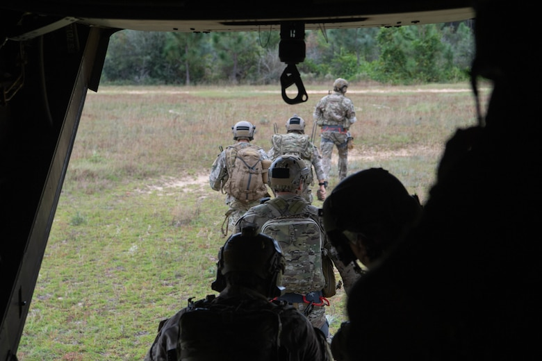We look out the ramp of a helicopter on the ground as a line of Special Tactics operators disembark and walk away from the helicopter.