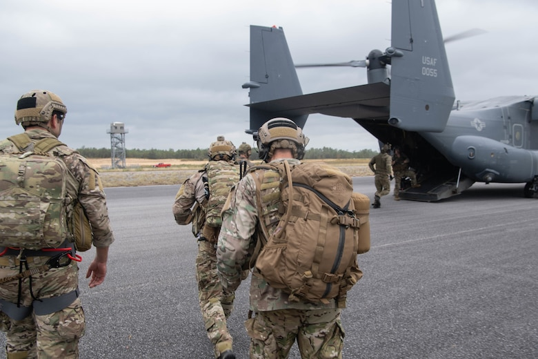 A trio of Special Tactics operators in the foreground with heavy packs walk toward a waiting dual-rotor helicopter ramp where another operator is approaching the ramp.