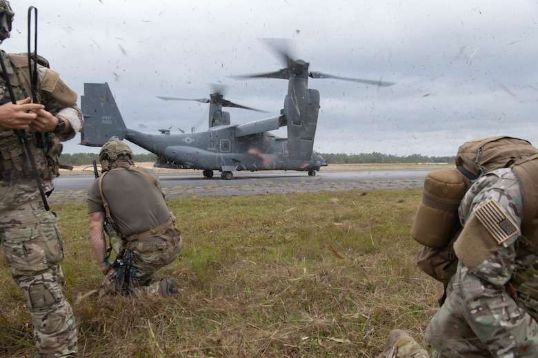 A trio of Special Tactics operators in the foreground brace as a dual-rotor helicopter a 100 feet away spins up its rotors prior to take-off.