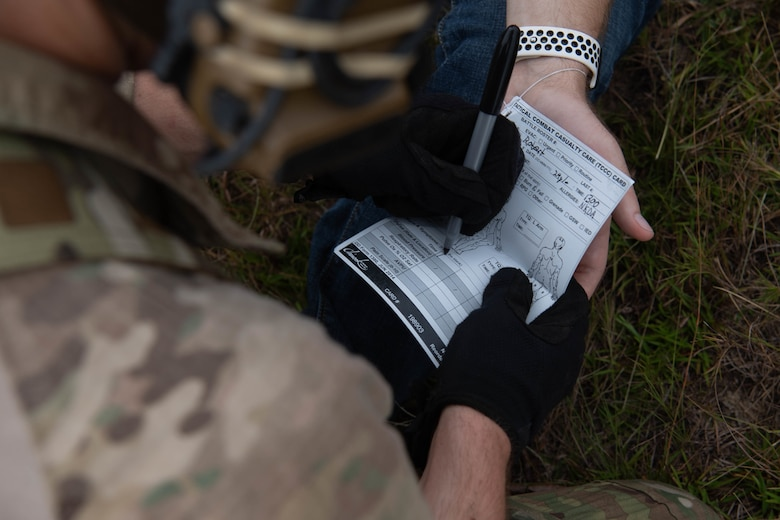 We look over the shoulder of a Special Tactics operator as his black-gloved hands write with a Sharpie on the lower half of a paper form that has been folded in the middle.