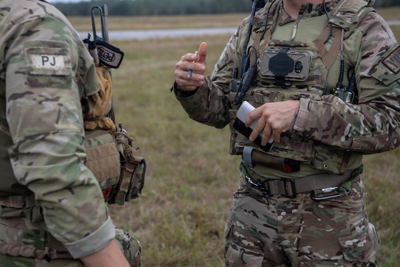 """From the side we see the torsos of two Special Tactics operators as they exchange information. The operator on the right is using his hands to make a point as he talks. We can see the """"PJ"""" shoulder patch insignia on the operator on the left indicating that he is a """"pararescue jumper."""""""