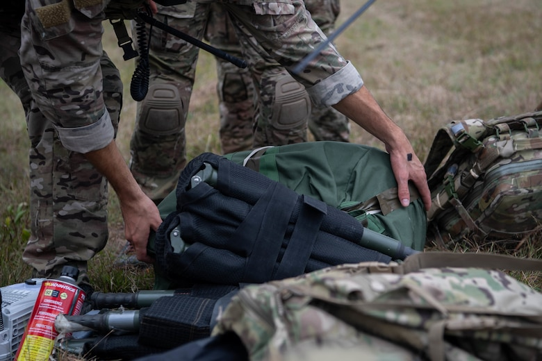 We see the arms of a Special Tactics operator on the left as he reaches down to pick up a folded-up dark green stretcher from a pile of equipment. We see the legs of another operator as he stands behind the operator reaching for the stretcher.