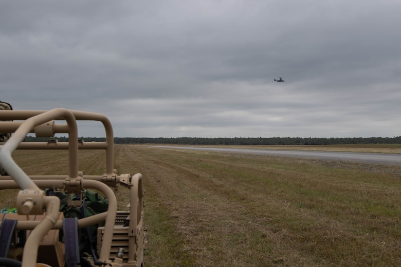Far off in the distance, a dual-rotor helicopter approaches a road that the Special Tactics operators are using as a landing zone. We can see some equipment sitting close to us as we look across the field at the helicopter.