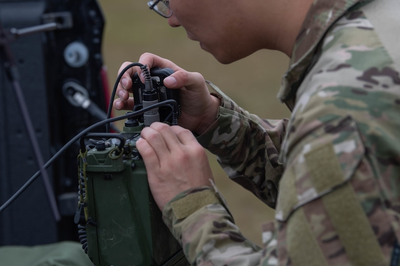 A Special Tactics operator wearing glasses works on black boxes containing radio gear. The operator is working to connect the boxes together so operators can talk to one another during the emergency response.