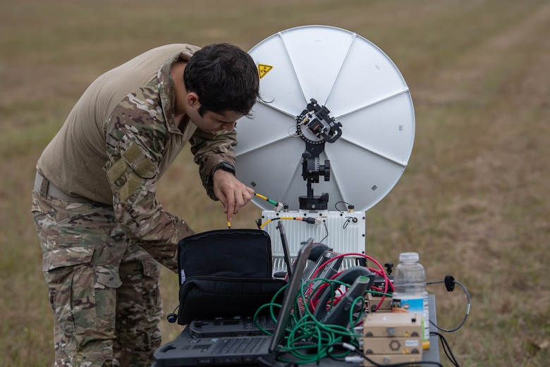 We are looking down a table at a small satellite dish pointing away from us. A Special Tactics operator is connecting radio equipment to the dish to aid communications during the disaster response exercise.