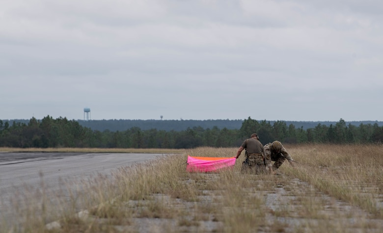 Two Special Tactics operators set up a bright pink panel beside the road in the distance to help aircraft locate the landing area.