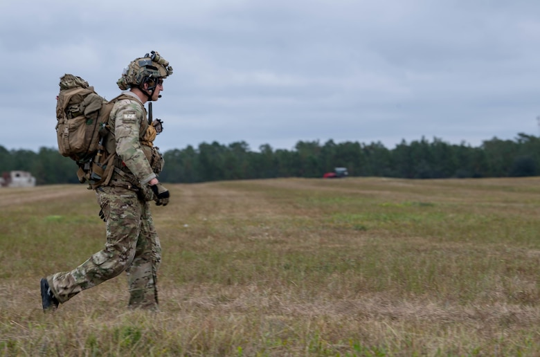 A Special Tactics operator walks close to us from from left to right across a field with a heavy pack. We see a large field of grass stretching off into the distance where it meets a tree line.