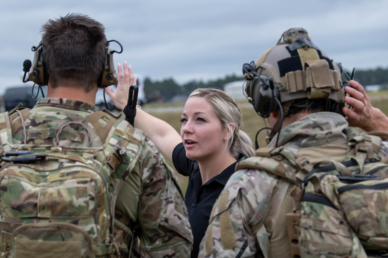 A blond woman in a black t-shirt can be seen talking to a pair of Special Tactics operators as we look between them over their shoulders at the woman gesturing toward the distance.