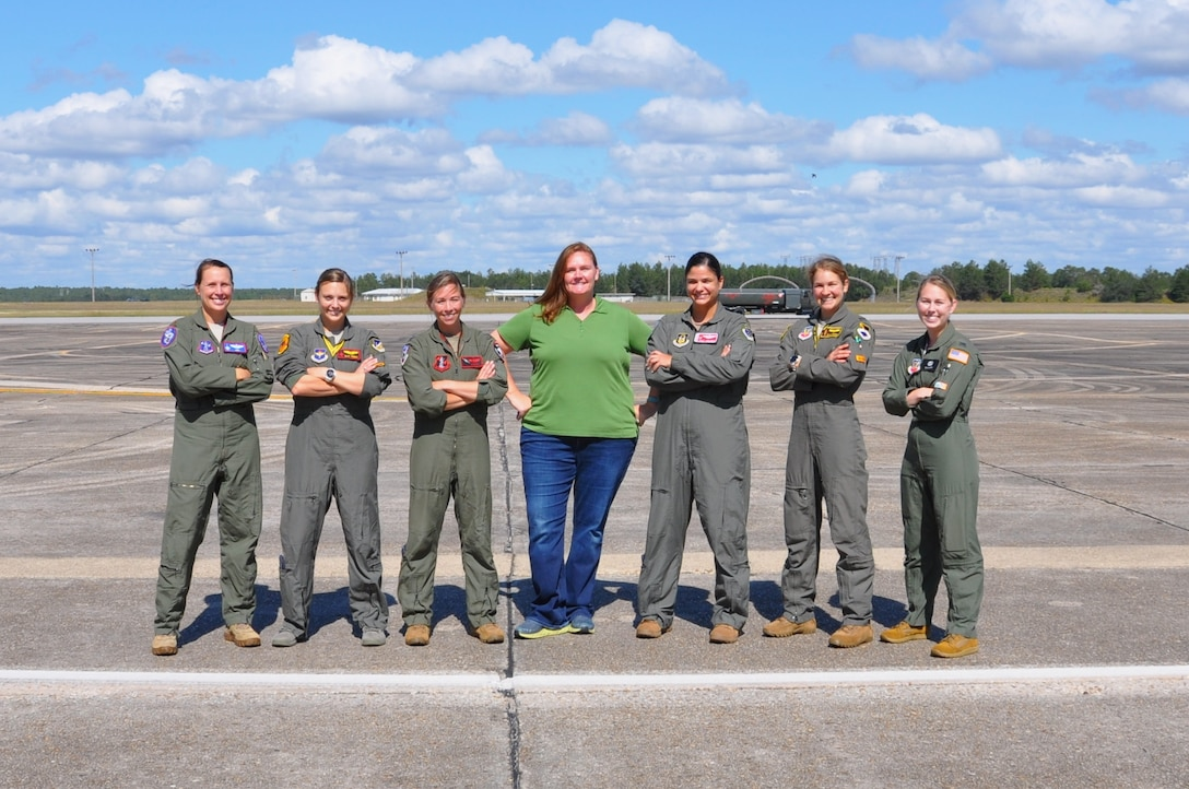 seven women stand on the flight line