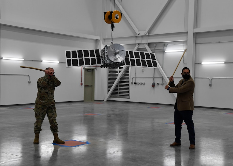 Director of the Air Force Research Laboratory Space Vehicles Directorate, Col. Eric Felt (left) and Benjamin Urioste, research engineer, prepare to break the satellite piñata, following the ribbon cutting ceremony to celebrate the opening of the directorate's Deployable Structures Laboratory at Kirtland Air Force Base, New Mexico, Oct. 29, 2020. (U.S. Air Force photo by Airman 1st Class Ireland Summers)
