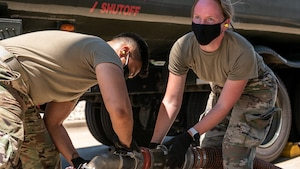 Airmen working with refueling equipment.