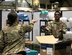A female soldier tosses a small box in the air toward a male soldier in a storage room.
