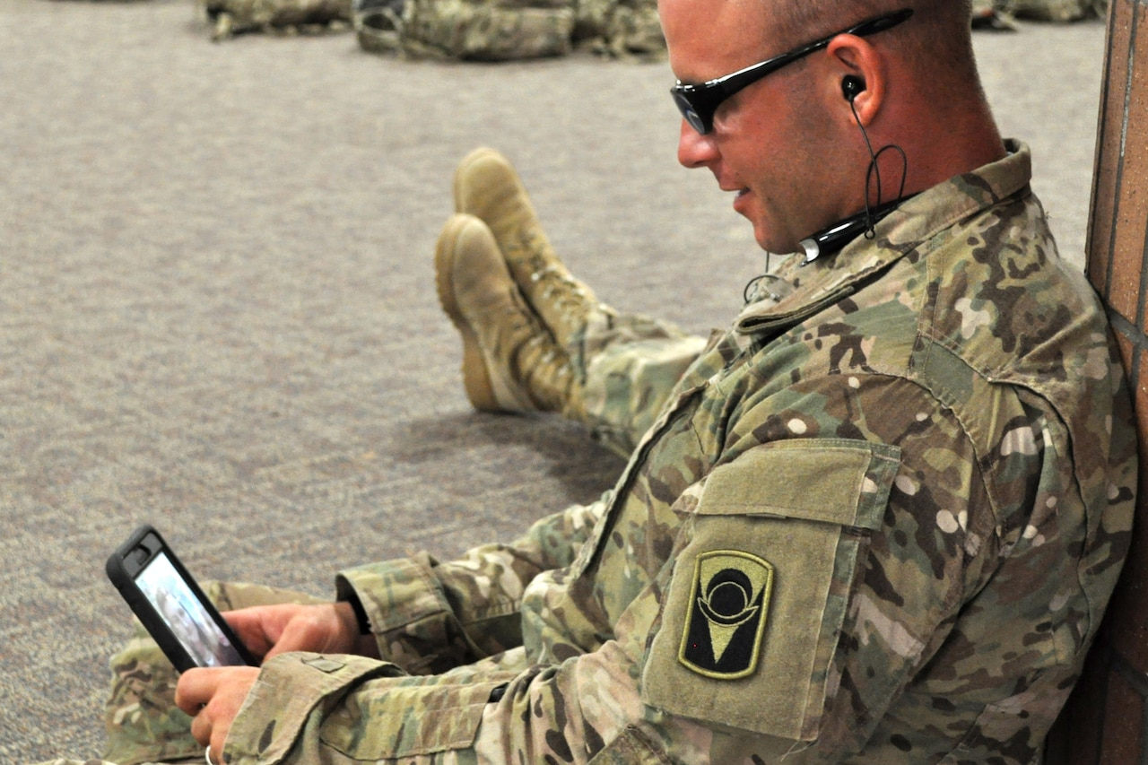A soldier uses an  app on his cellphone.
