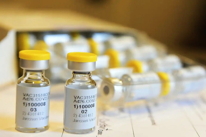 Two containers of a potential vaccine are in the forefront while several more are in the background in a tray.