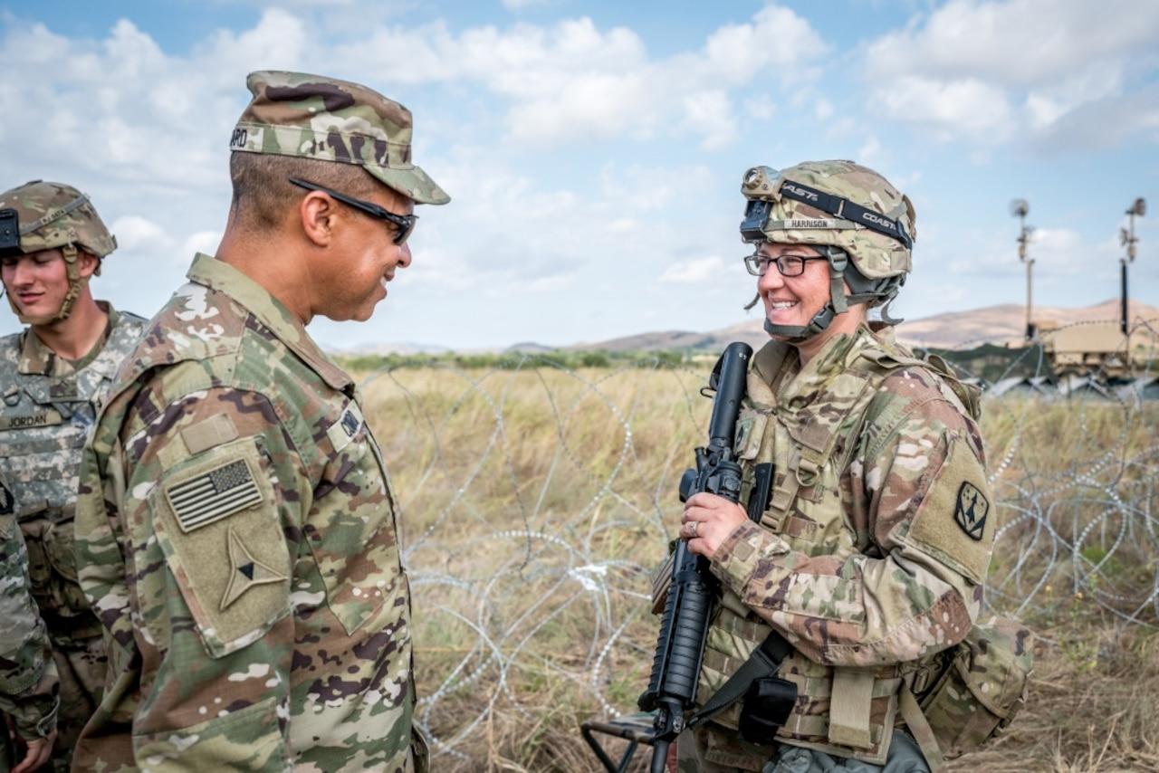 An older man in a military uniform talks to a young woman in a military uniform as they stand in a field.