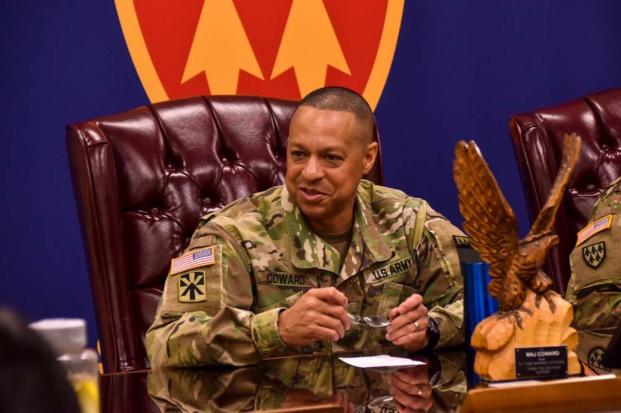 A man in a military uniform sits at a table in a large chair; he is holding a pair of glasses in his hands.