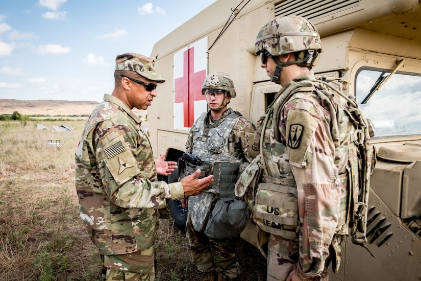 Three men stand beside a large vehicle bearing a red cross and talk.