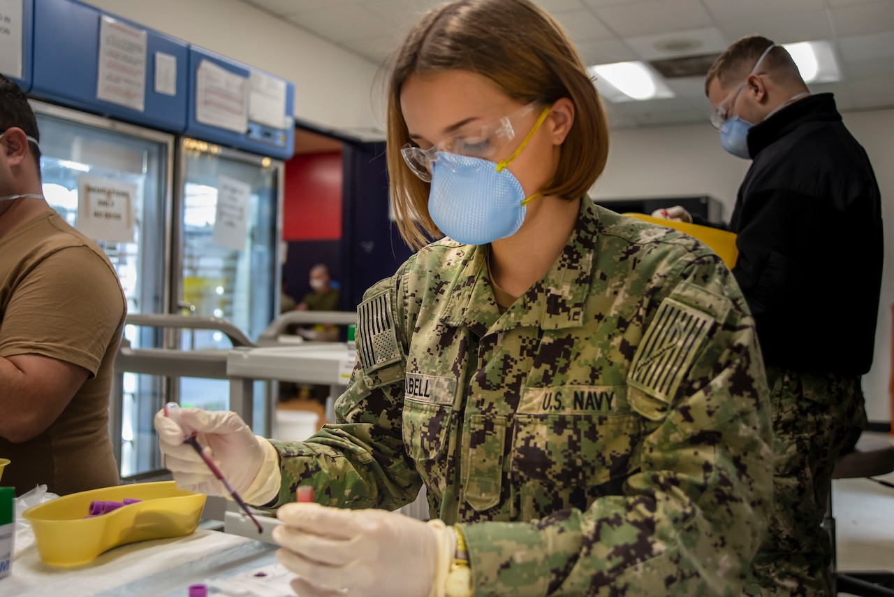 A female sailor handles a blood test.