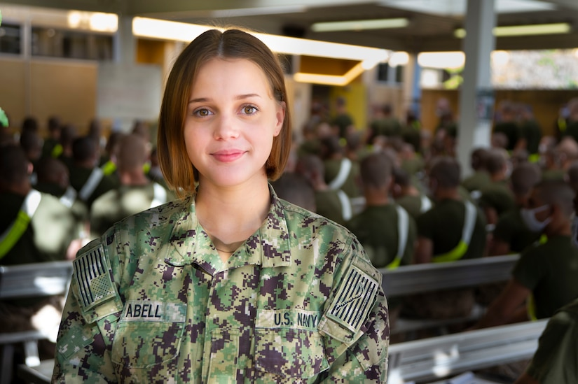 A female sailor poses for a photograph in front of Marine recruits.
