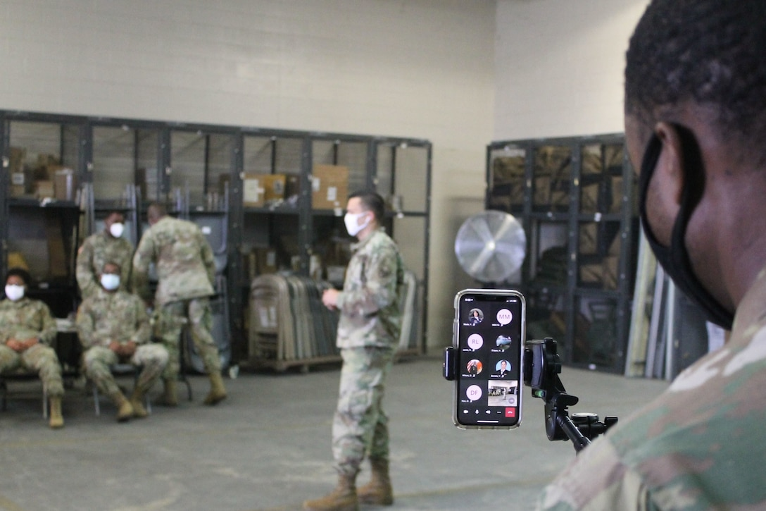 A U.S. Army Reserve Soldier monitors a cell phone during a live broadcast of primary marksmanship instruction for a battle assembly in Belle Chasse, Louisiana October 25, 2020.