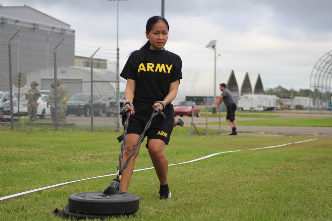 Spc. Ladey Omani, currently serving as a unit supply specialist for the 377th Theater Sustainment Command, pulls a 90-pound weight during training on the Army C