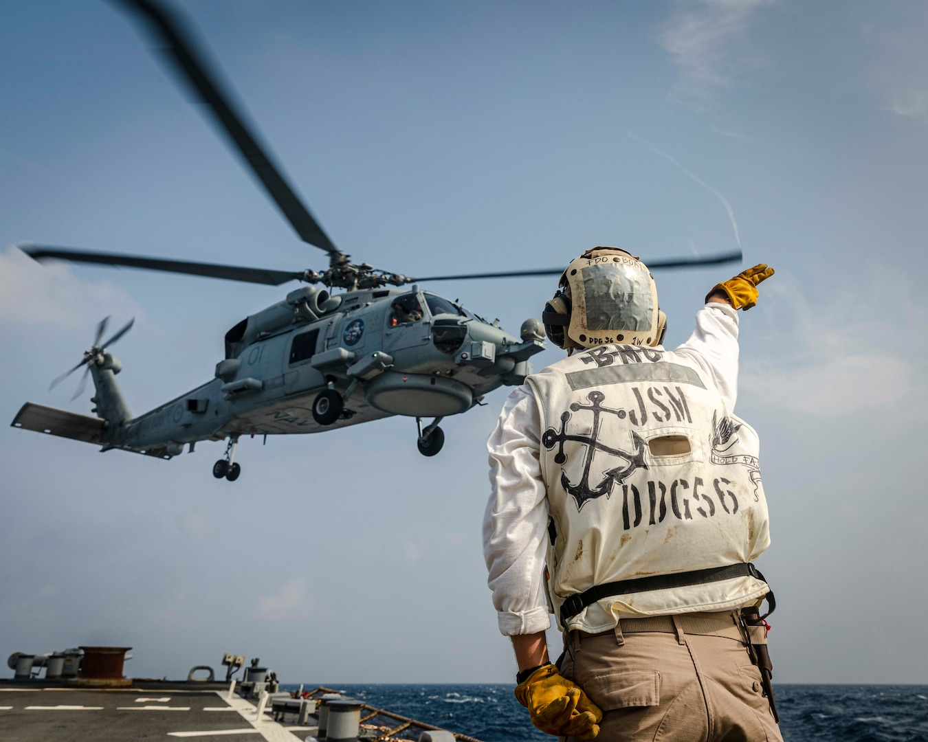 Chief Boatswain's Mate Juan Vigil, from Las Vegas, sends off an MH-60R Sea Hawk helicopter from the Royal Australian Navy Anzac-class frigate HMAS Ballarat (FFH 155) as it takes off from the flight deck aboard the Arleigh Burke-class guided-missile destroyer USS John S. McCain (DDG 56) during flight operations