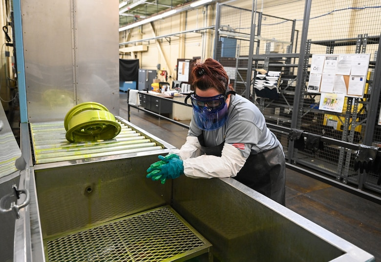 Peggy Archer, M1 Support Services nondestructive inspection lead waits for a piece of an aircraft to dry after it was dipped in a fluorescent penetrant on Oct. 29, 2020, at Columbus Air Force Base, Miss. The fluorescent penetrant is used to detect cracks in aircraft parts. (U.S. Air Force photo by Airman 1st Class Davis Donaldson)
