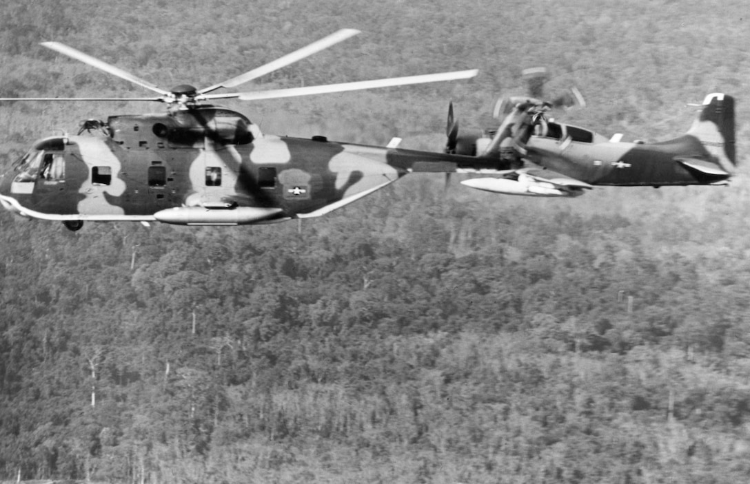 A camouflage-painted helicopter flies beside an airplane over a jungle.