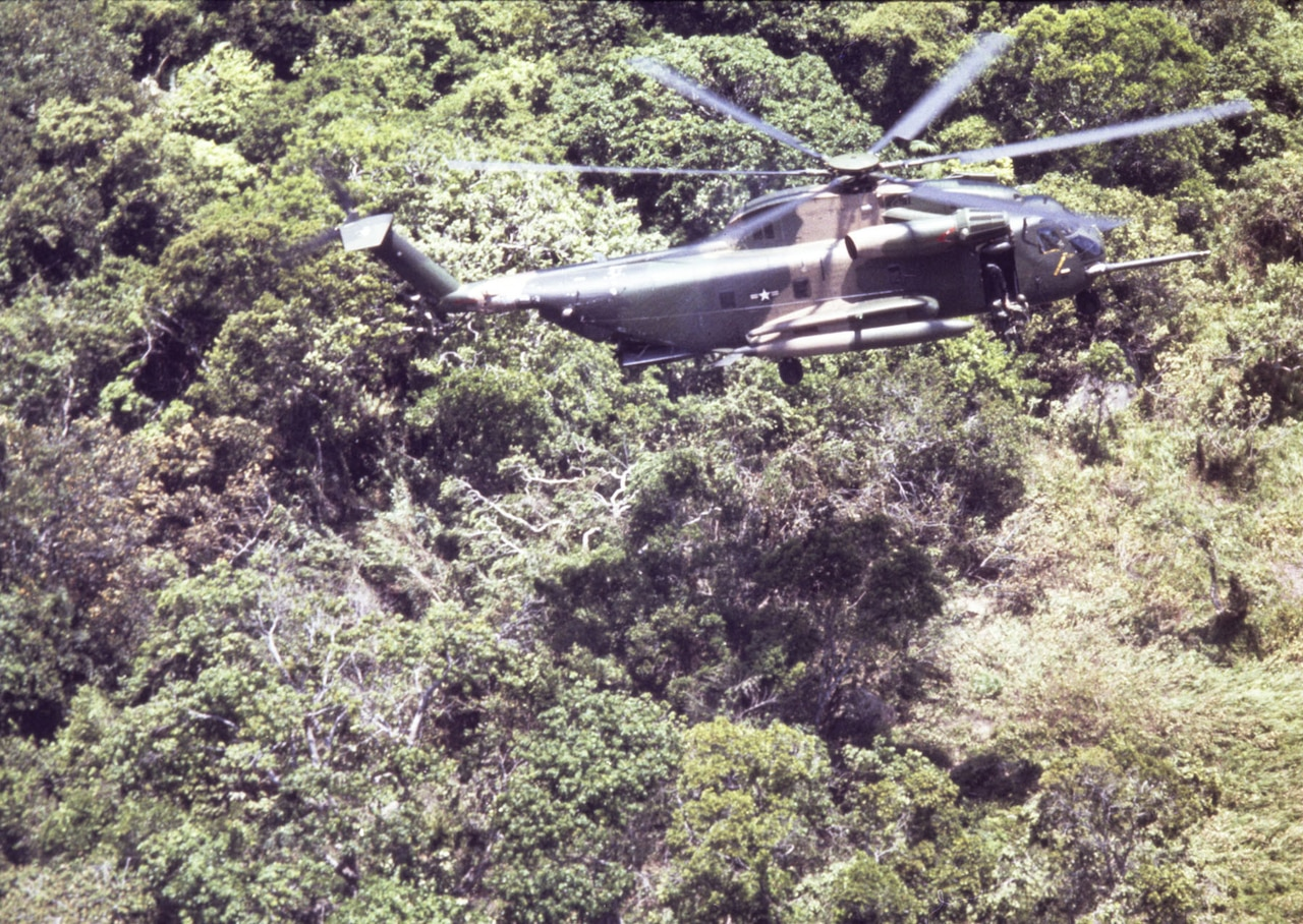 A helicopter hovers over a jungle.