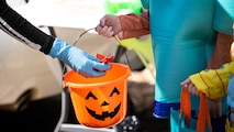 Airman Jonnica Blaylock, a Barksdale volunteer, places candy in a child's bucket during the Trunk or Treat event at Barksdale Air Force Base, La., Oct. 31, 2020.