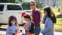 Chaplain (Maj.) Michael Johnson, 2nd Bomb Wing deputy wing chaplain, and his daughters, Erin, Megan and Grace use the sanitizer station during the Trunk or Treat event at Barksdale Air Force Base, La., Oct. 31, 2020.